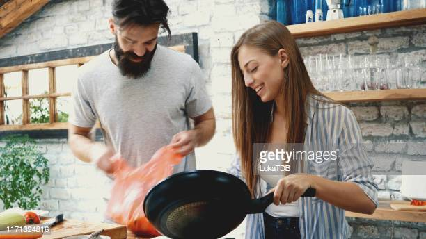 young couple making dinner together at home - kitchen after party stock pictures, royalty-free photos & images