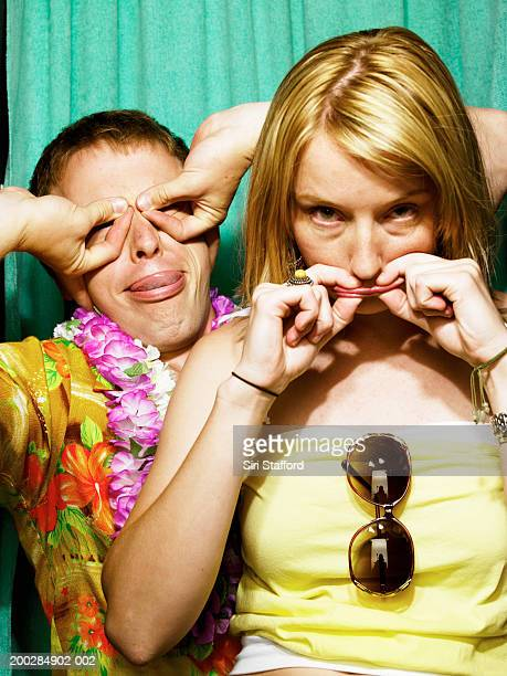 Young couple making faces in photo booth