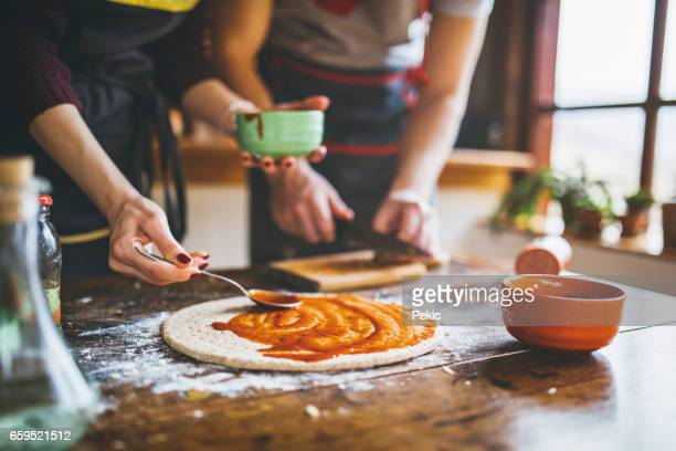 Young couple making fresh pizza in kitchen