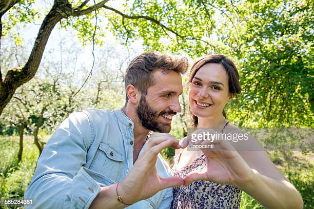young couple making heart shape with hands, looking at camera smiling - gesturing stock pictures, royalty-free photos & images