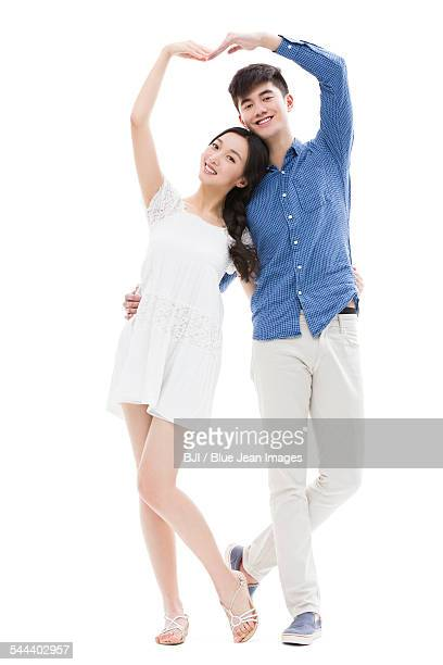 Young couple making heart shape with their arms