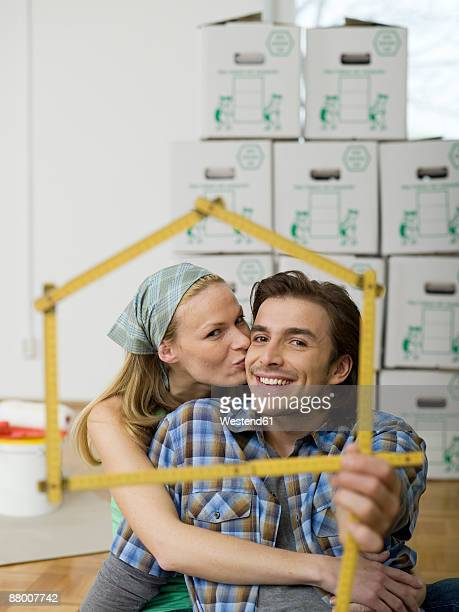 Young couple making house shape with folding ruler, woman kissing man, portrait