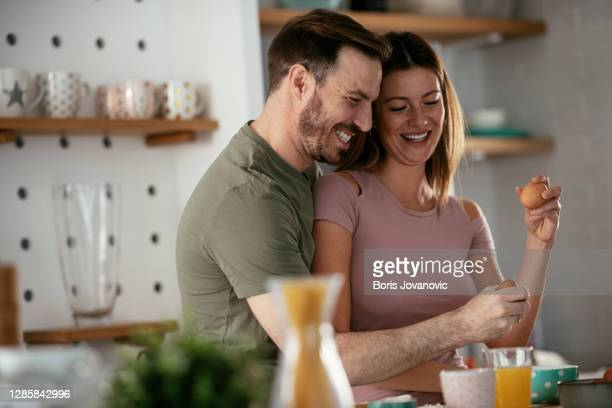 young couple making sandwich at home