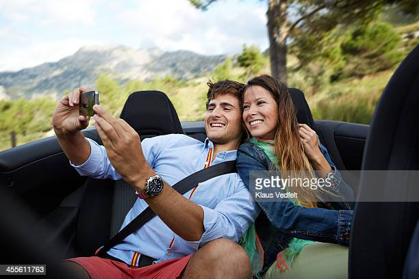 young couple making selfie on the backseat of car - klaus vedfelt mallorca stock pictures, royalty-free photos & images