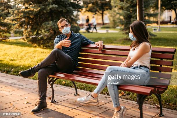 young couple making social distance on date - bench stock pictures, royalty-free photos & images