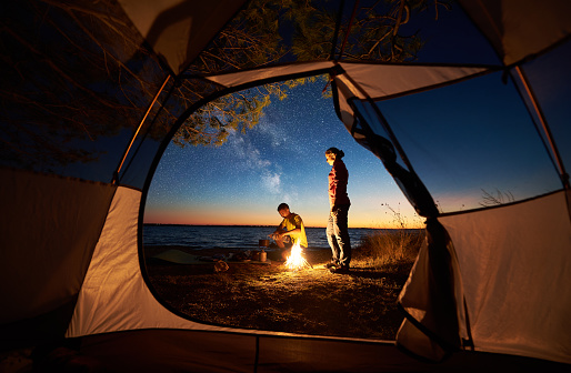 Young couple man and woman having rest at tourist tent and burning campfire on sea shore near forest 1002768222