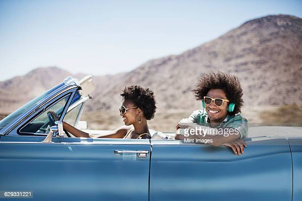 a young couple, man and woman in a pale blue convertible on the open road  - americana azul fotografías e imágenes de stock