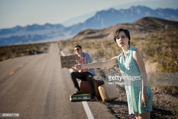 A young couple, man and woman, on a tarmac road in the desert hitchhiking, with a sign saying Vegas or Bust.