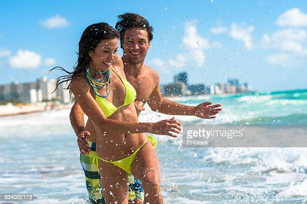 Young Couple Man and Woman Playing in Surf at Beach