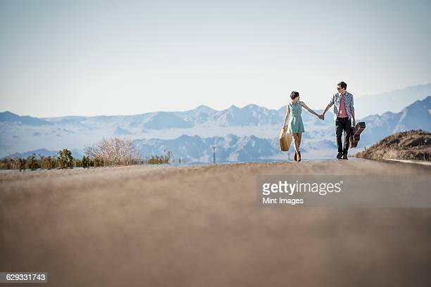 A young couple, man and woman walking hand in hand on a tarmac road in the desert carrying cases.