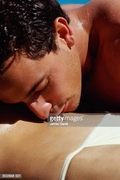 Young couple, man kissing woman's bare stomach, close-up