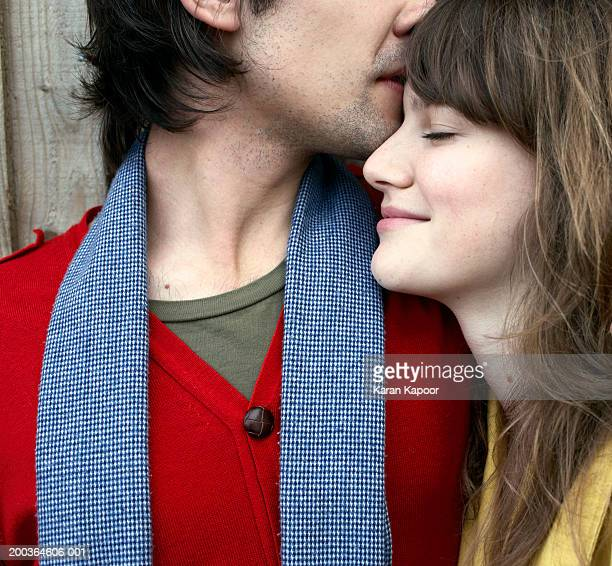 Young couple, man nuzzling woman, profile, close-up