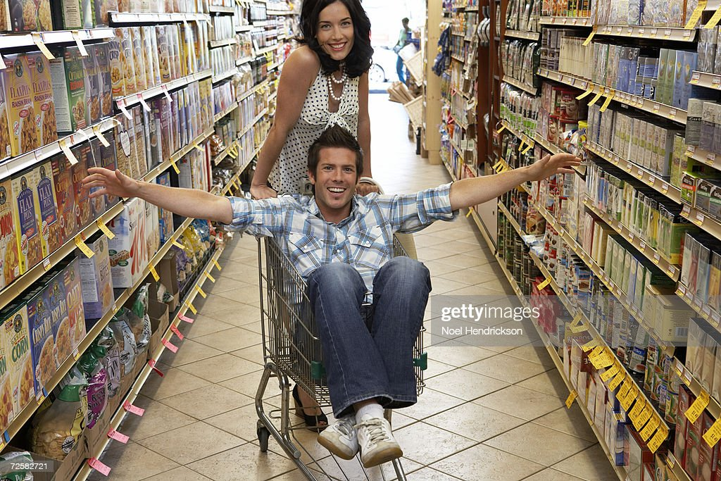 """""""Young couple, man sitting in shopping trolley in supermarket"""" : Stock Photo"""