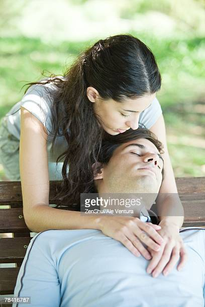 young couple, man sleeping on bench while woman puts arms around him from behind - man bending over from behind stock photos and pictures