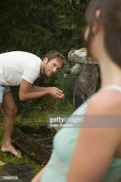 'Young couple, man taking water from fountain'