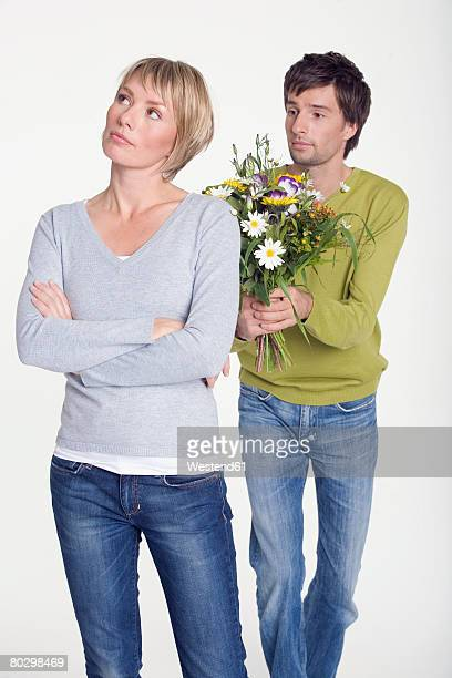 Young man giving flowers to woman