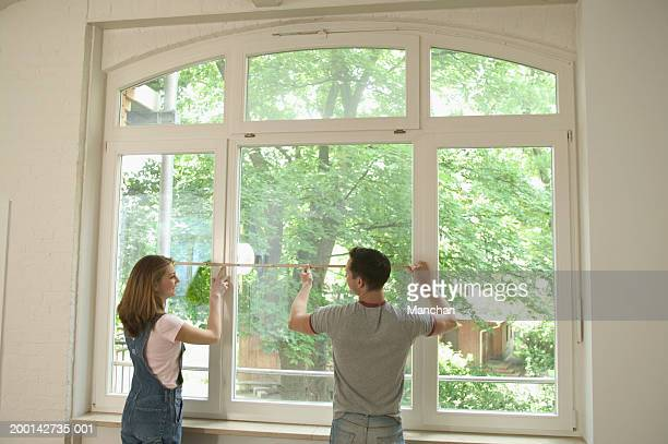 Young couple measuring window space, rear view