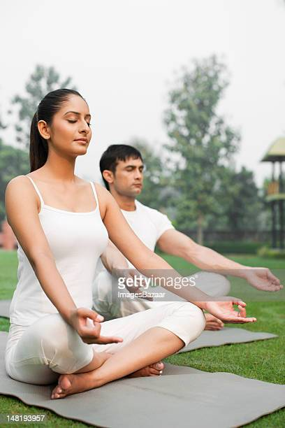 Young couple meditating in garden