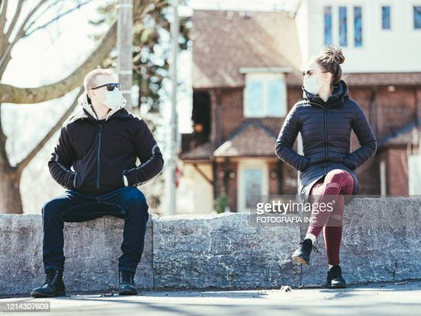 covid-19, young couple meeting outside - social distancing stock pictures, royalty-free photos & images