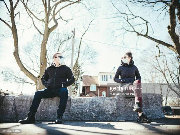 covid-19, junges paar trifft sich draußen - abstand halten stock-fotos und bilder