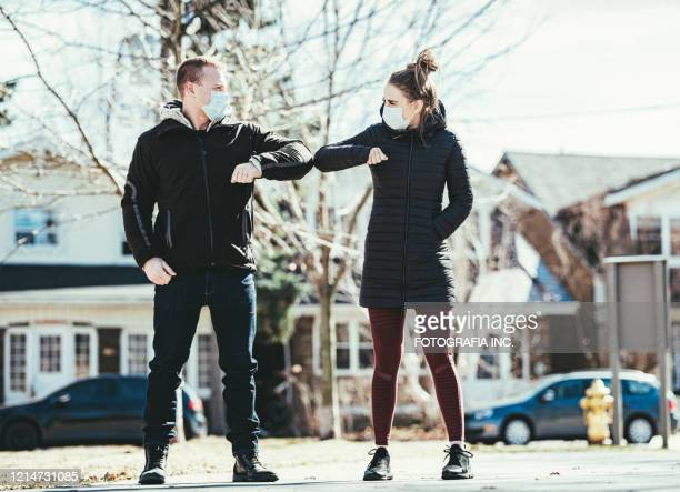 covid-19, young couple meeting outside - elbow bump stock pictures, royalty-free photos & images
