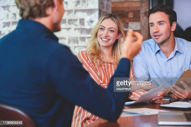 young couple meeting with an advisor or business person - interview event stock pictures, royalty-free photos & images