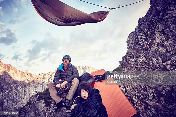 young couple mountainside, looking at view, innsbruck, tyrol, austria - 岩壁 ストックフォトと画像