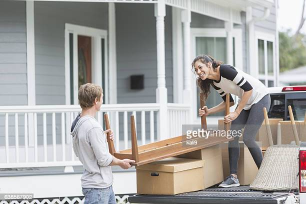 Young couple moving furniture into new home