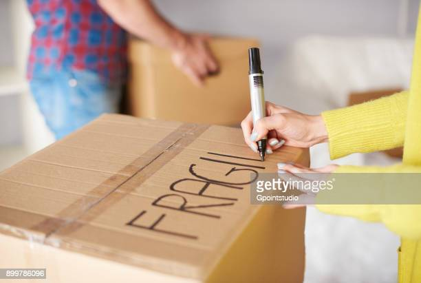young couple moving home, young woman labelling cardboard box, mid section - labeling stock photos and pictures