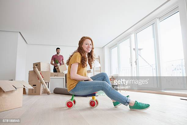 Young couple moving into new flat, woman sitting on toy cart