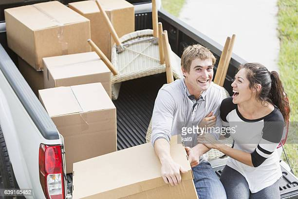 Young couple moving into new home, on pickup truck