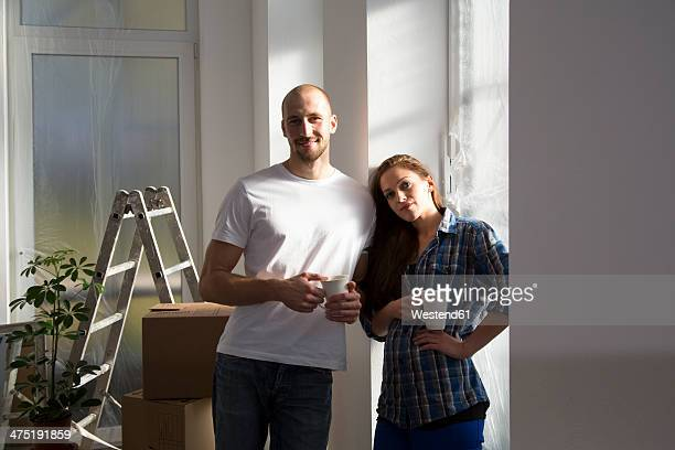 Young couple moving into new home, taking a coffee break