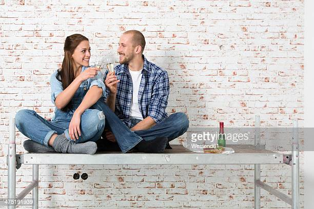 Young couple moving into new home, toasting with champagne glasses