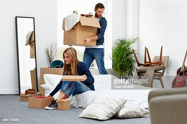 young couple moving into their new house - arranging stock pictures, royalty-free photos & images