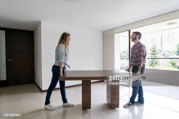 casal jovem, movendo-se para sua nova casa carregando uma mesa de jantar enquanto conversando e se divertindo - mesa mobília - fotografias e filmes do acervo