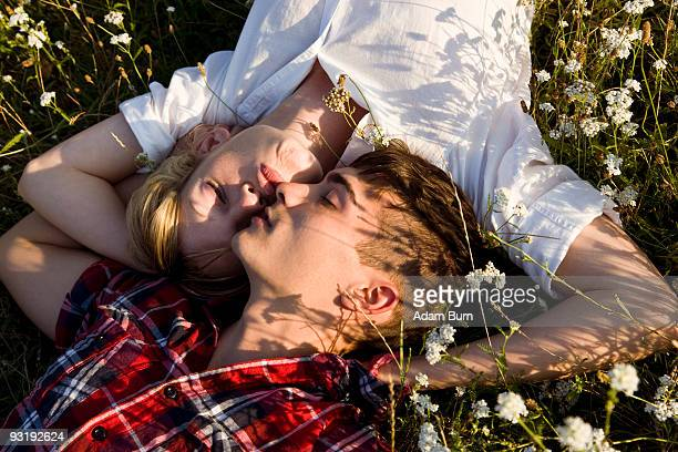 A young couple napping in a field
