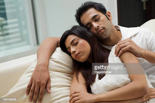 young couple napping on sofa - heterosexual couple stock pictures, royalty-free photos & images