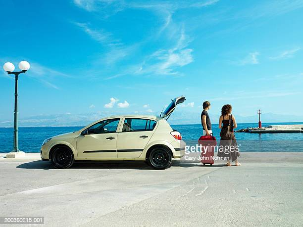 Young couple near car with luggage looking at ocean, rear view