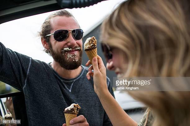 young couple next to jeep messily eating ice cream cones - eis essen stock-fotos und bilder
