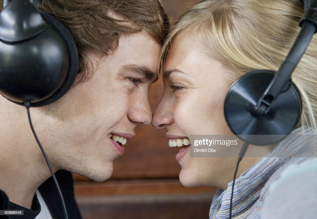 young couple nose to nose with headphones on : Stock Photo