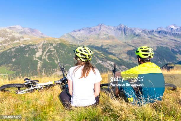 young couple of biker sitting in the meadow in the mountain. - italia stockfoto's en -beelden