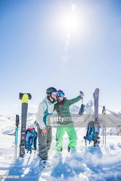 Joven pareja de esquiadores haciendo una fotografía selfie