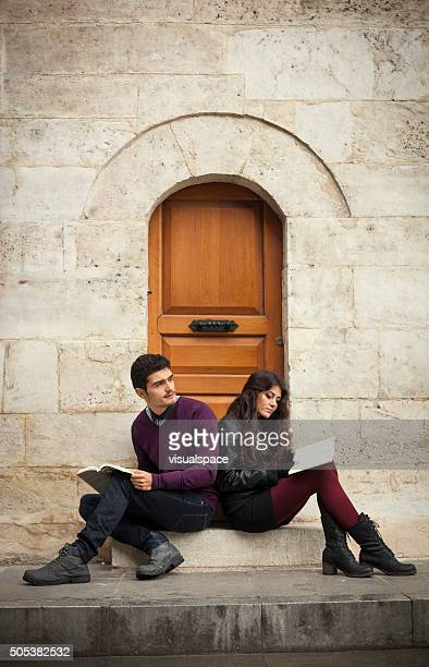 Young Couple of Travellers Reading Outside Their Apartment