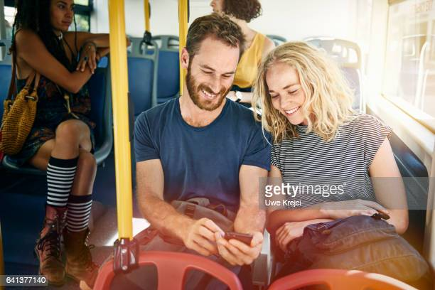 Young couple on a bus looking at smart phone