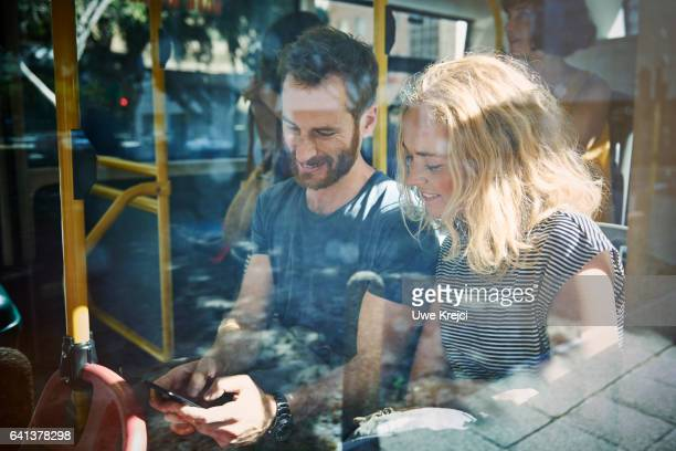 young couple on a bus looking at smart phone - transporte público imagens e fotografias de stock