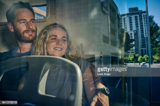 Young couple on a bus looking out of the window