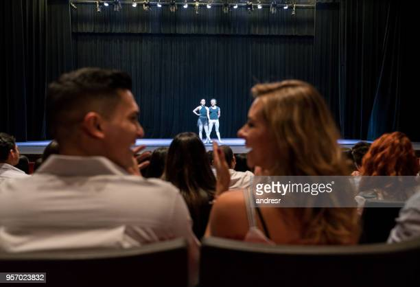 young couple on a date at ballet applauding and looking at each other smiling - theatrical performance stock pictures, royalty-free photos & images