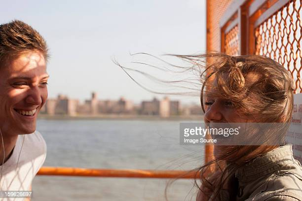 Young couple on a ferry, wind blowing hair