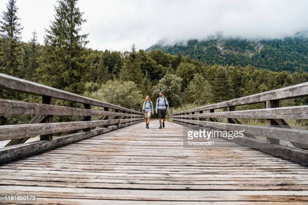 young couple on a hiking trip walking on wooden bridge, vorderriss, bavaria, germany - 接近する 女性 ストックフォトと画像