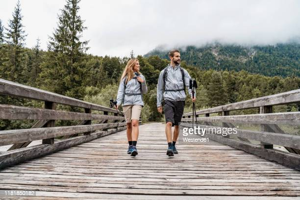 young couple on a hiking trip walking on wooden bridge, vorderriss, bavaria, germany - 接近する ストックフォトと画像